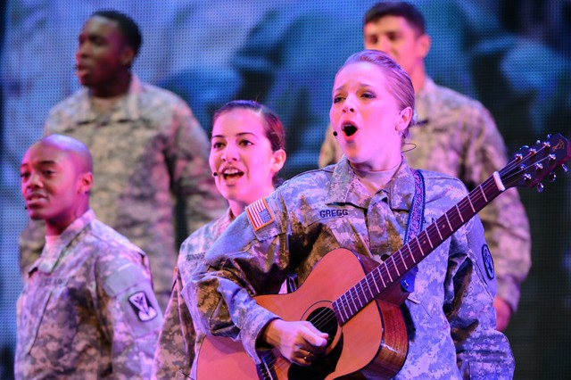 "Spc. Kelly Gregg of Fort Bliss, Texas, plays guitar and leads the cast of the U.S. Army Soldier Show in a chorus of ""Some Nights"" during an April 21 performance at Fort Sam Houston Theatre on Joint Base San Antonio-Fort Sam Houston, Texas. Sgt. Craig Moton of Suwon Air Base, South Korea, and Sgt. Ena Torres of Fort Hood, Texas, flank Gregg on the front row. New Mexico Army National Guard Sgt. Quentin Dorn and Pvt. Alberth Madrigal of Fort Drum, N.Y., are in the backdrop."