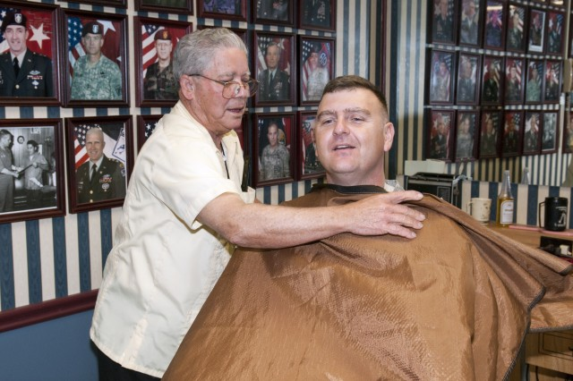 Travis Bell, XVIII Airborne Corps barber, puts on a barber's cape for his next customer as he prepares to give a haircut Apr. 16 at the barber shop located in XVIII Abn. Corps headquarters. For 45 years, Bell has professionally been giving military haircuts to hundreds of thousands of servicemembers on Fort Bragg. (Photo by Spc. Paul A. Holston/XVIII Abn. Corps PAO)
