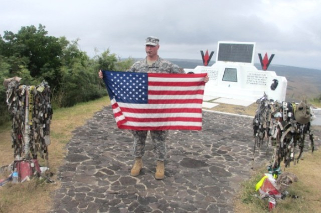 Master Sgt. Tim Parrish, 247th Military Police Detachment, holds an American flag at the memorial atop Mount Suribachi on Iwo Jima on March 22, 2013.