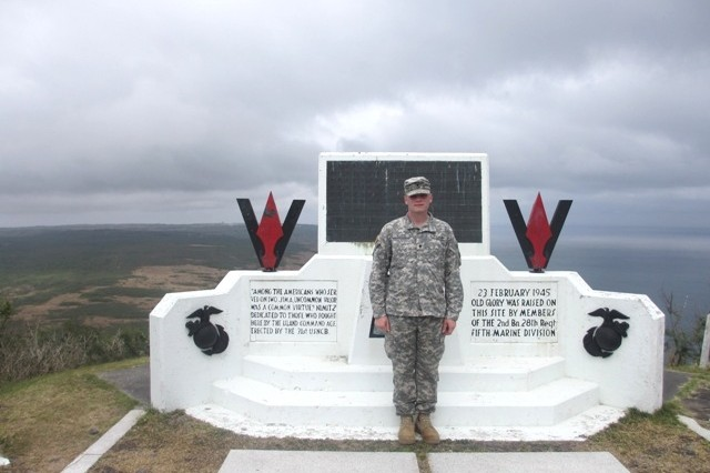 Spc. Nathan Allen, who is assigned to the 24th Military Police Detachment on Torii Station, stands in front of the memorial at the top of Mount Suribachi on Iwo Jima on March 22, 2013.