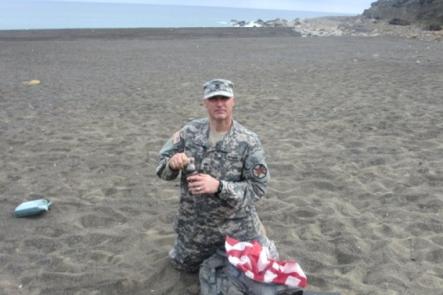 "Master Sgt. Tim Parrish, who is assigned to the 24th Military Police Detachment on Torii Station, collects sand from ""attack beach"" on Iwo Jima on March 22, 2013."