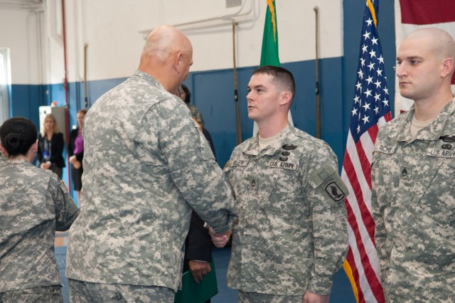 U.S. Army Chief of Staff Gen. Ray Odierno presents the Army Commendation Medal for Valor to Staff Sgt. Jesse Miller during an award ceremony in Caserma Ederle in Vicenza, Italy, May 1, 2013.  Miller received the award for his courageous actions during combat operations in Afghanistan. (U.S. Army photo by Staff Sgt. Teddy Wade/ Released)