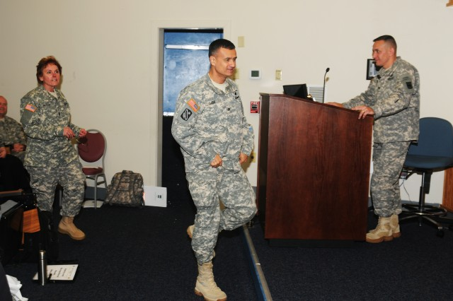 Col. Edwin Lugo and Command Sgt. Maj. Jenny Bryan, 3rd Brigade, 94th Training Division commander and senior noncommissioned officer, rush the stage to accept the 80th Training Command Fiscal Year 2012 level three Commander's Excellence in Safety Award on behalf of one of their subordinate units, Regional Training Site - Maintenance, Fort Hood, Texas. during the 80th Training Command's second Semi-annual Safety and Occupational Health Advisory Council meeting held in Richmond Va., May 4, 2013. The brigade also won the level one award.