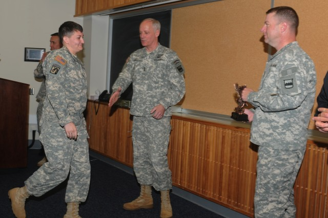 Maj. Gen. Bill Gerety, commander 80th Training Command, extends a hand while Staff Sergeant Jessica Hebler, Headquarters 2nd Brigade, 94th Training Division, steps forward to accept an Exceptional Individual Safety Award from Command Sergeant Major James Wills, 80th TC senior enlisted leader during the command's second Semi-annual Safety and Occupational Health Advisory Council meeting in Richmond, Va. May 4, 2013.