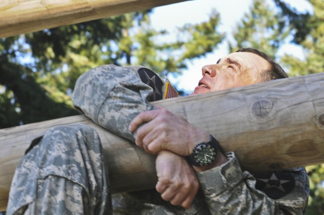 """A senior enlisted leader struggles to maintain his grip on the """"Weaver"""" obstacle in the first event of the Mangudai Warrior Challenge at Joint Base Lewis-McChord, Wash., May 1. The exercise draws its history from Special Forces units of the Mongol Empire dating back to the 13th Century. It began May 1 and lasted 58-straight hours with minimal food and sleep for the warriors. (U.S. Army photo by Sgt. Ryan Hallock)"""