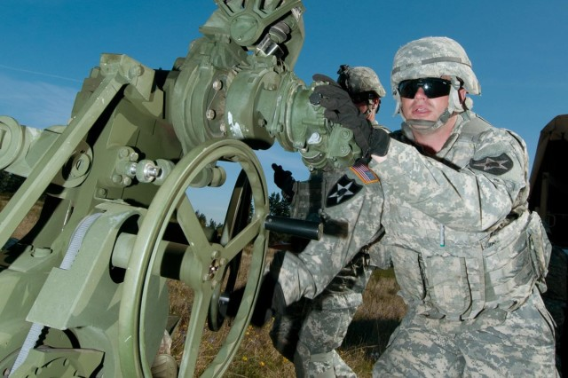 Spc. Nicholas Davis, gunner, 2nd Battalion, 17th Field Artillery Regiment, readies his weapon, the M777 Howitzer, on the firing line during a live fire training exercise on Joint Base Lewis-McChord, Wash., May 2. The Batteries of the Steel Battalion spent the day training and live firing rounds from howitzers as part of a twice-a-year requirement to certify on the weapon.