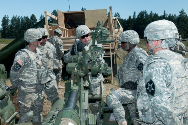 First Sergeant James Cannon, B Battery, 2nd Battalion, 17th Field Artillery Regiment, talks and shares words of motivation and encouragement to a M777 Howitzer crew  on the firing line during a live fire training exercise on Joint Base Lewis-McChord, Wash., May 2., The Batteries of the Steel Battalion spent the day training and live firing rounds from howitzers as part of a twice-a-year requirement to certify on the weapon.