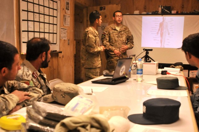 Spc. Jacob R. Garza, a medic with Security Force Assistance Team 8, Texas Army National Guard, discusses the human body with Afghan Border and Uniformed Police during medical training April 29 at Forward Operating Base Spin Boldak, Afghanistan. The train the trainer class taught police leaders advanced knowledge of the human body and field medical procedures. (U.S. Army photo by Staff Sgt. Shane Hamann, 102nd Mobile Public Affairs Detachment.)