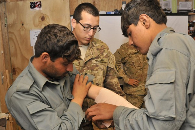 Spc. Jacob R. Garza, a medic with Security Force Assistance Team 8, Texas Army National Guard, observes as Afghan Border and Uniformed Police demonstrate treating a broken bone during medical training April 29 at Forward Operating Base Spin Boldak, Afghanistan. The train the trainer class taught police leaders advanced knowledge of the human body and field medical procedures. (U.S. Army photo by Staff Sgt. Shane Hamann, 102nd Mobile Public Affairs Detachment.)