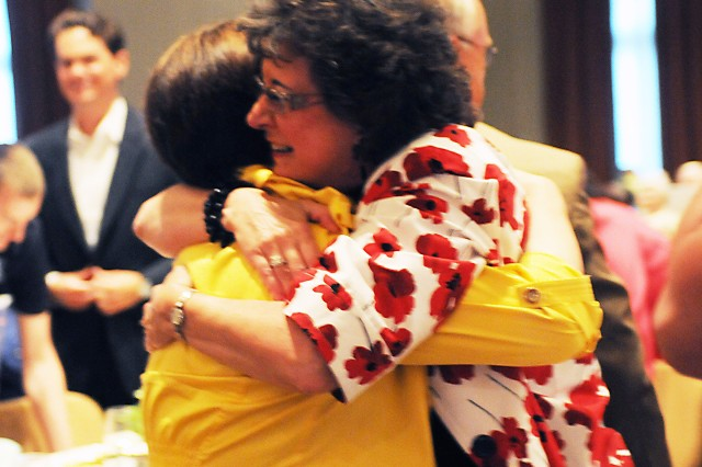 Julie Pelletier, media specialist at Loyd Elementary School, and Julita Martinez, Loyd principal, hug after finding out their school won the Partners in Education Partnership of the Year Award April 30. Partnership of the Year is the top award in the PIE program.