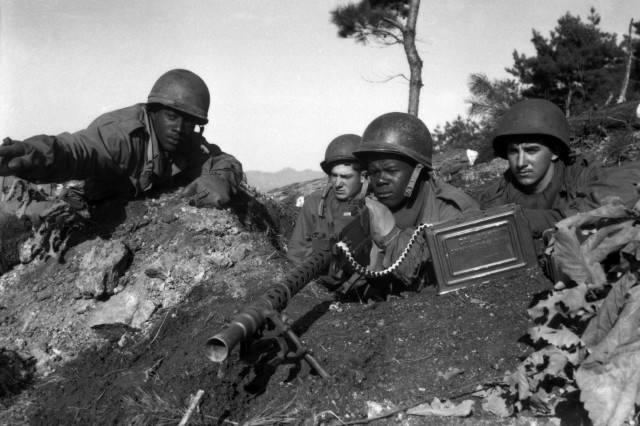 Fighting with the 2nd Infantry Division north of the Chongchon River, Sgt. 1st Class Major Cleveland (left), weapons squad leader, points out Communist-led North Korean position to his machine crew, Nov. 20, 1950.