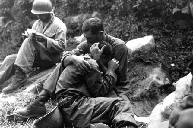 A grief-stricken American infantryman, whose buddy has been killed in action, is comforted by another Soldier. In the background a medic methodically fills out casualty tags, Haktong-ni, Korea, Aug. 28, 1950.