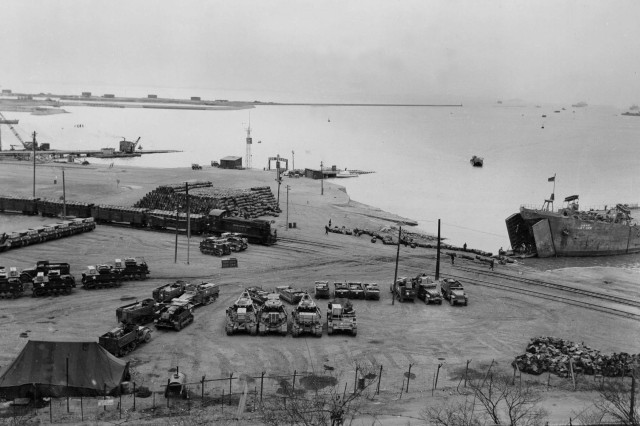 The Port of Inchon, Korea, is a hub of activity on Jan. 25, 1953. A landing beach and two finger piers for dispatching small craft are visible. There is open storage area in foreground and a tank farm in background.