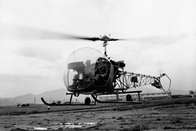 "Maj. Michael J. Stoke, executive officer, 79th Ordnance Aircraft Maintenance Battalion, U.S. Eighth Army, and Capt. Charles C. Blake, a chaplain known as the ""flying chaplain,"" depart by helicopter to visit 79th Ordnance units in Korea, June 8, 1953."