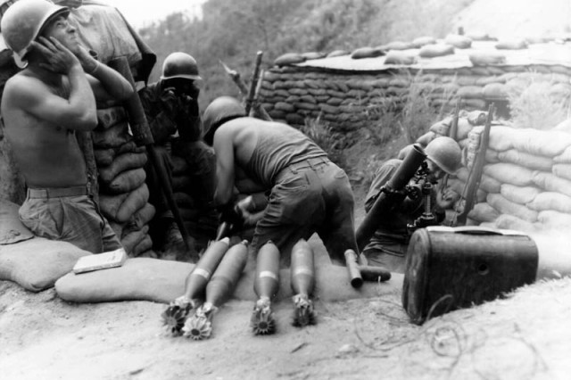 """Soldiers of the 81-mm Mortar Platoon, Co. D, 2nd Battalion, 5th Infantry Regiment, U.S. Eighth Army, blast Communist positions in the """"Punchbowl"""", Korea, Aug. 12, 1952."""