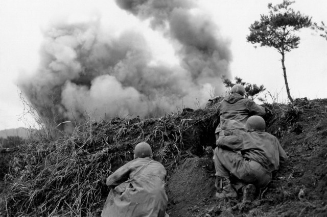 Men of the 77th Engineer Combat Company blast at Communist troops taking cover in caves imbedded along steep banks of the Hantan River. 11 Apr 1951.