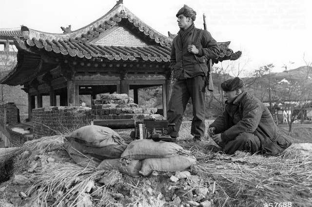 Cpl. Donald C Blackman of Longsport, ID (sitting), and Cpl. Joseph L. Lasleur of Stillman, Valley, IL, keep a sharp lookout for Chinese Communists troops at their post near the front lines in Korea.  Both are members of the 27th Infantry Regiment, 25th Infantry Division. January 29th, 1951.