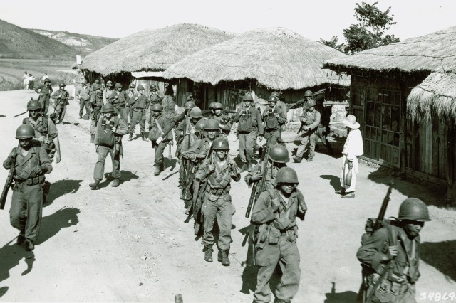 Men of the 32nd Infantry Regiment, 7th Division, advance through a Korean village, six miles southeast of Inchon, Korean.  September 18th, 1950.