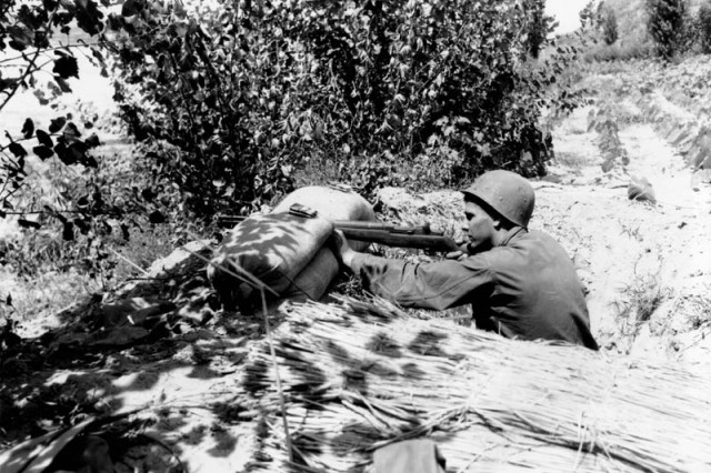 Pfc. Letcher V. Gardner fires on an emplacement of the Communist-led North Koreans along the Naktong River near Chingu, Korea, Aug. 13, 1950. Gardner is assigned to the 1st Cavalry Division's Company D, 8th Cavalry Regiment.