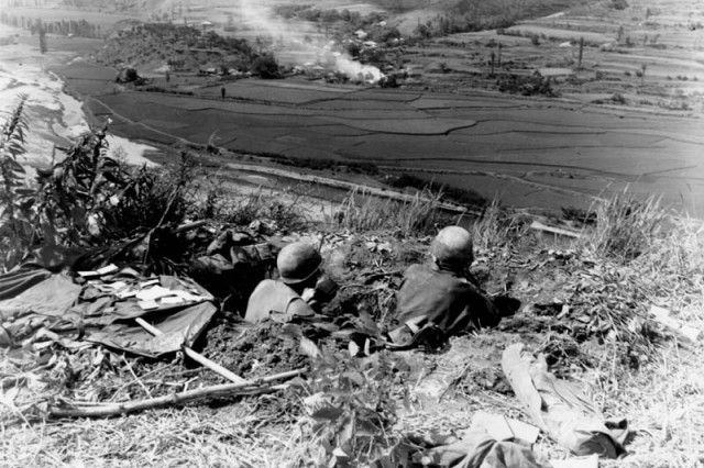 Pfc. Robert Smith of Springfield, Colo., left, and Pvt. Carl Fisher of Ponca, Okla., 27th Infantry Regiment, are dug in and firing at Communist-led North Korean positions, Sept. 4, 1950.