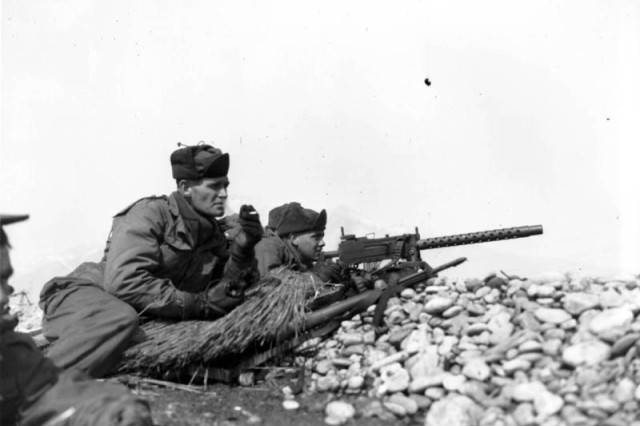Men of the 25th Infantry Division's Company K, 35th Regimental Combat Team, fire a light machine gun in support of a rifle platoon attacking Chinese Communist positions north of the Han River, Korea, March 7, 1951.