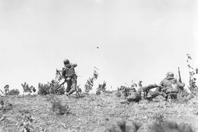 Second Lt. Ralph Barnes throws a hand grenade at Chinese Communist positions, as UN troops launch an offensive attack against the Communists near Uijong-Bu, Korea, March 23, 1951. Barnes, of Arlington, Va., is a platoon leader in the 3rd Infantry Division's 1st Platoon, Company C, 15th Infantry Regiment.