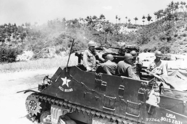 A 105-mm self-propelled howitzer, manned by five Soldiers from Cody, Wyo., speeds another projectile into Communist lines in Korea, July 1, 1951. The men, all artillerymen in Battery B, 300th Armored Field Artillery Battalion, X Corps, are (left to right); Sgt. 1st Class Allen J. Helms, section chief; Cpl. Joseph Stair, gunner; Sgt. Richard N. Null, lanyard man; Cpl. Robert C. Smith, artilleryman.