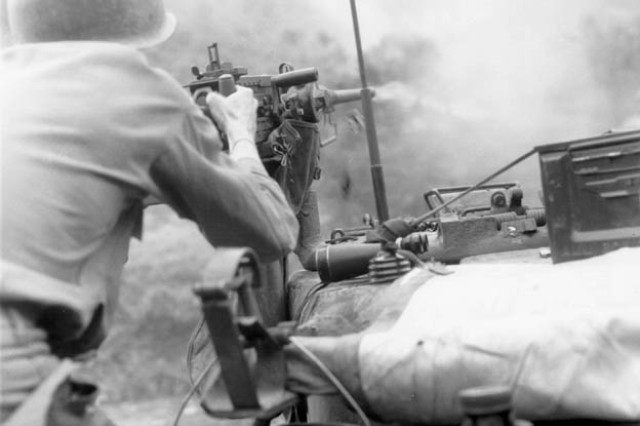 Sgt. Douglas D. Tompkins of the 24th Infantry Division's Tank Company, 5th Regimental Combat Team, fires a .50-caliber machine gun at Communist-held positions during an assault against the Chinese Communist forces along the east central front, Korea, July 14, 1951.