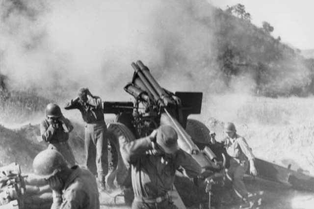Soldiers of Battery C, 936th Field Artillery Battalion, U.S. Eighth Army, fire the 100,001st and 100,002nd shell at Chinese Communist position near Choriwon, Korea, Oct. 10, 1951.