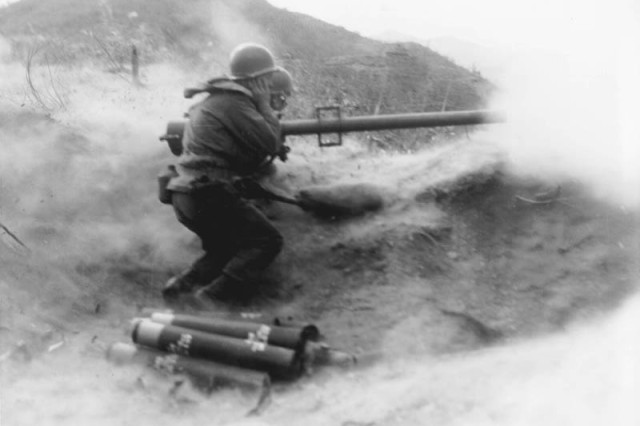 Powder, smoke and dust billow as a recoilless rifle team of the 3rd Infantry Division's Company D, 7th infantry Regiment, fire their weapon at a Chinese Communist  position on Hill 200, near Qnmong-Myon, Korea, Nov. 9, 1951.