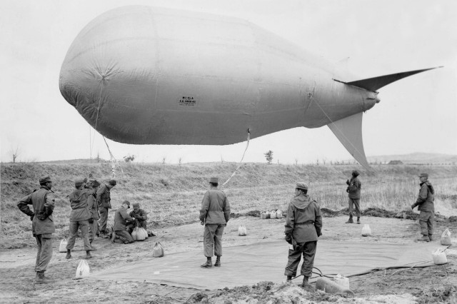 """Soldiers of Company C, 14th Engineer Combat Battalion, 8th U.S. Army, ground the M-1 """"VLA"""" barrage balloon, which is used to mark the Panmunjon Military Armistice Conference perimeter in Korea, March 22, 1952. The balloon is 35 feet long and 14 feet in diameter. It holds 3,000 cubic feet of helium gas, and is elevated to a height of 1200 feet."""