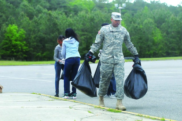 First Sgt. Gregory Marrisette, Alpha Company, 832nd Ordnance Battalion, 59th Ord. Brigade, carries bags of trash collected from the grounds of Petersburg High School May 4.  Marrisette, Alpha Co. Commander Capt. Forrest Clay and 10 other Soldiers volunteered to help National Honor Society students with a community service project.