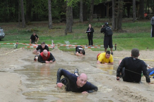 Competitors in Hohenfels' Warrior Challenge cool off in the mud crawl, May 4.