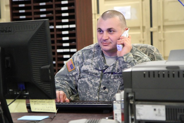 Spc. David Meskhishvili, who works in stock control, helps a customer on the phone. All Supply Support Activity paperwork goes through this section. The 2nd Brigade Combat Team SSA is operated by logisticians from Headquarters and Headquarters Company, 210th Brigade Support Battalion.