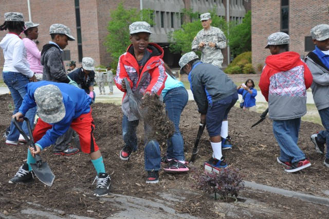 Students from Killian Elementary School help plant trees in the 1st Battalion, 34th Infantry Regiment battalion area April 27. The tree planting was part of the school's community outreach program and the battalion's self-help beautification project.