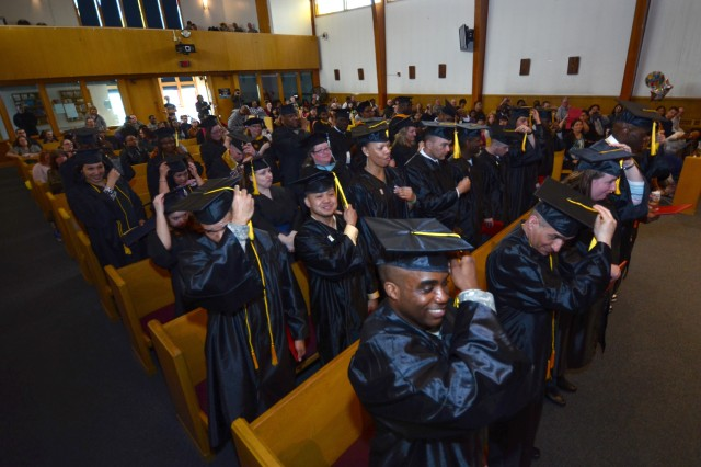 A happy group of graduates move their tassels as they celebrate with Family and friends their academic achievements during the Army Education Center's 2013 Joint College Commencement event Monday in the Southern Lights Chapel on Fort Wainwright.