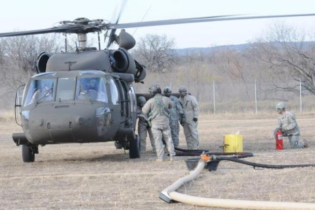 Pilot Chief Warrant Officer 3 Trevor Jon Saari and Co-Pilot Chief Warrant Officer 4 William Noyer of the 166th Aviation Brigade wait in a Black Hawk helicopter while their Crew Chief Staff Sgt. Duston Watson monitors members of the 13th Expeditionary Sustainment Command's 53rd Quartermaster Company conducting fuel support operations at North Fort Hood, Texas, at the new forward area refueling point.  (Photo by 1st Lt. Kat Kaliski, 166th Aviation Brigade, Division West Public Affairs)