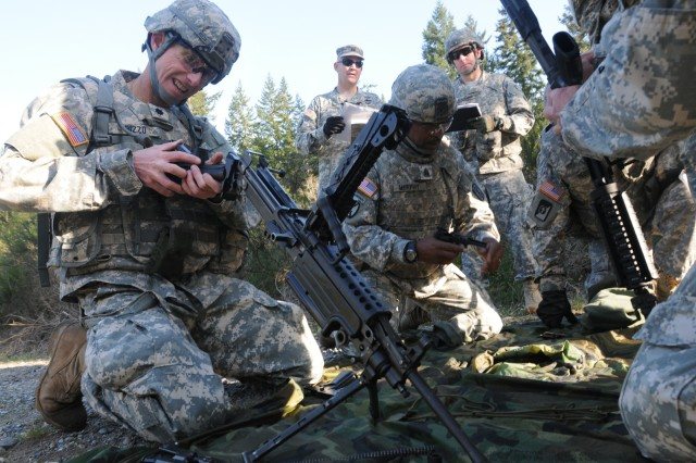 """JOINT BASE LEWIS-MCCHORD, Wash. """"   Lt. Col. Christopher Rizzo (left), Headquarters and Headquarters Battalion, I Corps, assembles an M249 squad automatic weapon during a quarterly """"Courage Challenge,"""" May 2.  The series of Courage Challenge events are designed to build esprit de corps among JBLM's senior leaders and use basic Soldier skills in a field setting. It also serves as a forum for senior leaders to provide input to JBLM leadership on training and command challenges. (Photo by Staff Sgt. Mark Miranda, 5th Mobile Public Affairs Detachment)"""