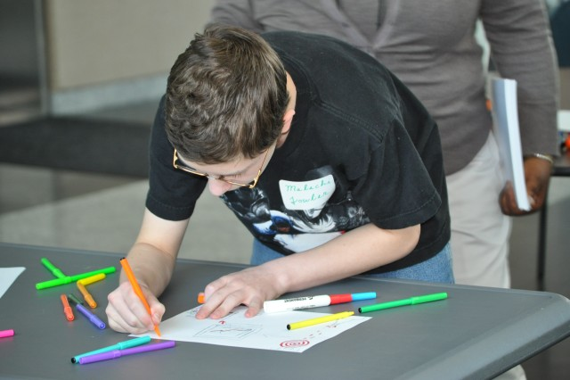 "Malachi Fowler, 13, draws a picture of what he believes his dad, Jonathan Fowler, chief of the Mounted Maneuver Division, Army Evaluation Center, does at work during the ""Take our Daughters and Sons to Work Day"" held at the Hollis Building on Aberdeen Proving Ground April 25, 2013."