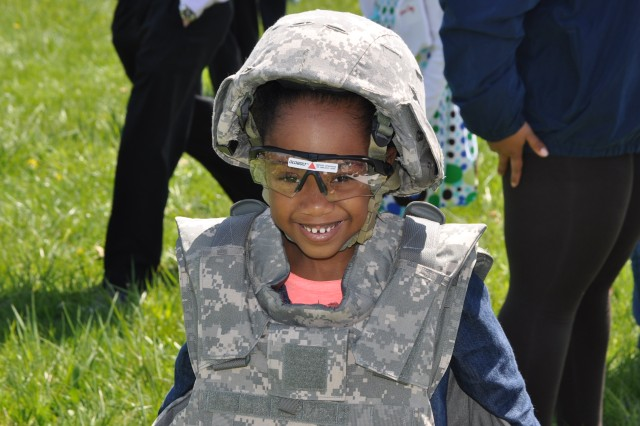 "Dominique LeGrand, 6-year-old daughter of Sgt. 1st Class Shaniqua Davis, military evaluator, U.S. Army Evaluation Center, tests out Army field gear during the ""Take our Daughters and Sons to Work Day"" held at the ATEC Headquarters on Aberdeen Proving Ground April 25, 2013."