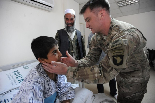 Sayed Anbia looks at U.S. Army 1st Lt. Dustin Stuart, physician assistant, Task Force Gladiator, Headquarters and Headquarters Battalion, Combined Joint Task Force-101, 101st Airborne Division (Air Assault), while he checks his neck for cancer as Anbia's father Ghulum Sayeed looks on during a visit to the Korean Hospital, Bagram Air Field, May 4. Anbia was diagnosed with Stage IIB classical Hodgkin's lymphomia and is receiving treatment due to the combined efforts of medical personnel from TF Gladiator and the Korean Hospital. If the chemotherapy is successful, Anbia has a 90-percent chance of living for the next five years. (U.S. Army National Guard photo by Staff Sgt. Jerry Saslav, 129th Mobile Public Affairs Detachment)