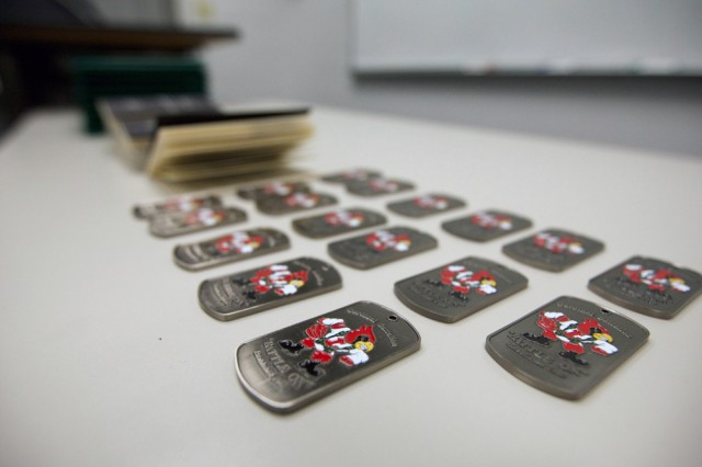 University of Louisville Cardinal Battalion coins sit on a table to be presented to commissioning Cadets. Photo by Steve Arel/U.S. Army Cadet Command