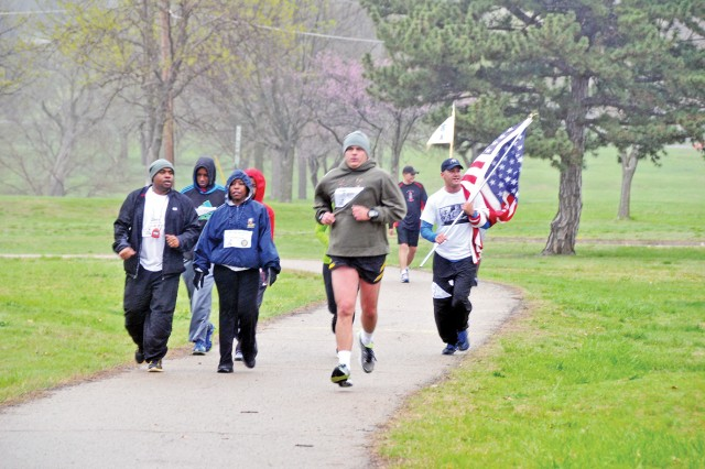 Sgt. Bella Johnson, 1st Bn., 28th Inf. Regt., 4th IBCT, 1st Inf. Div., far right, runs with an American flag, during a Run for the Fallen event May 4 at Riley's Conference Center, Fort Riley, Kan. Runners participated as a way to show honor to the memory of fallen Soldiers.