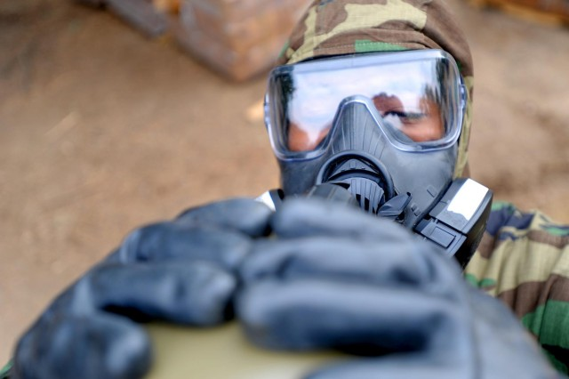 Equipment Operator Constructionman Ken Carter, a Seabee from Naval Mobile Construction Battalion (NMCB) 3, takes a drink from his canteen while wearing a gas mask during a chemical, biological and radiological (CBR) drill to test the team's ability to react to enemy CBR attacks.