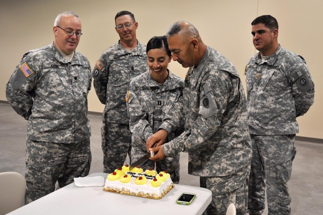 The command staff of the 2206th and 2208th Mobilization Support Battalions watch as the youngest and oldest soldiers of the battalions, Capt. Ginette Bocanegra and Sgt. 1st Class Lorenzo Sifuentes, make the initial cut into the cake.