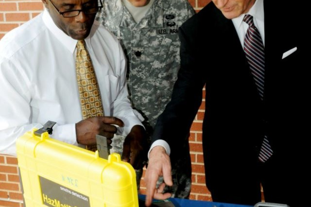 (Left) Glenn Simpkins, Incident Response Training Department instructor, discusses the use of the HazMatID 360, advanced portable chemical identifier, with Secretary of the Army John McHugh May 9 at Fort Leonard Wood, Mo., as Lt. Col. Gregory Borcherding looks on.