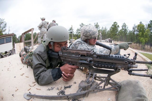 Indian Army RFN Anil Pawe, an infantryman with the 99th Mountain Brigade, and Spc. Henry Vaillancourt, a paratrooper with the 82nd Airborne Division's 1st Brigade Combat Team, partner up to fire an M249 Squad Automatic Weapon May 4, 2013, at Fort Bragg, N.C.  Vaillancourt is familiarizing Pawe with the American machine gun prior to field training as part of the annual U.S. - India Yudh Abhyas training exercise.  (U.S. Army photo by Sgt. Michael J. MacLeod)