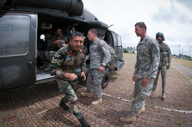 Brig. Gen. Ashok Dhingra, a military attache' with the Indian Army, exits a UH60 Black Hawk helicopter following an aerial tour of field training facilities hosted by the 82nd Airborne Division May 3, 2013, at Fort Bragg, N.C.  He and Brig. Gen. Jagdish Chaudhari (seated), received the tour at the beginning of Yudh Abhyas 2013, the latest in a series of annual training exercises between the armies of the United States and India.  (U.S. Army photo by Sgt. Michael J. MacLeod)