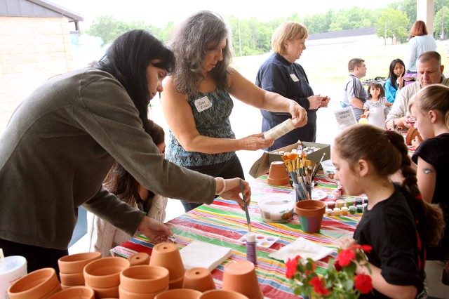 Volunteers and survivors work side-by-side to paint memory pots during the U.S. Army Space and Missile Defense Command/Army Forces Strategic Command-sponsored Survivor Outreach Services Spring Fling May 11 at the Redstone Arsenal, Ala., activity field.