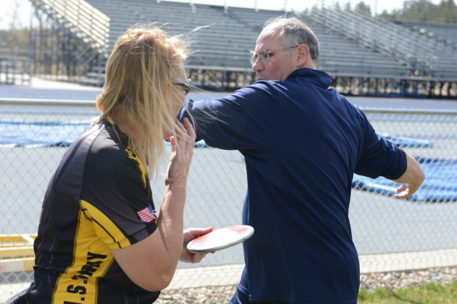 Coach Doug Garner demonstrates the finer points of discus throwing to Chanda Gaeth.